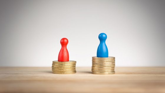 Game pieces standing on coins represent the gender pay gap