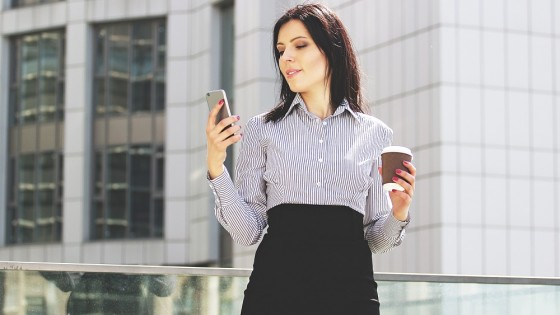 Open for communication. Portrait of confident and beautiful business woman in smart casual wear using her phone while drinking coffee against office building.