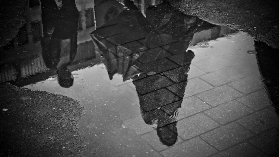 Shadow of people stood in the rain from a puddle