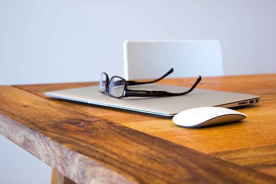 Macbook,glasses and a wireless mouse sat on a modern wooden desk