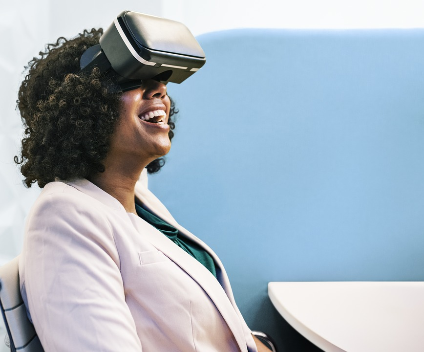 A woman sat in an office with a VR headset on