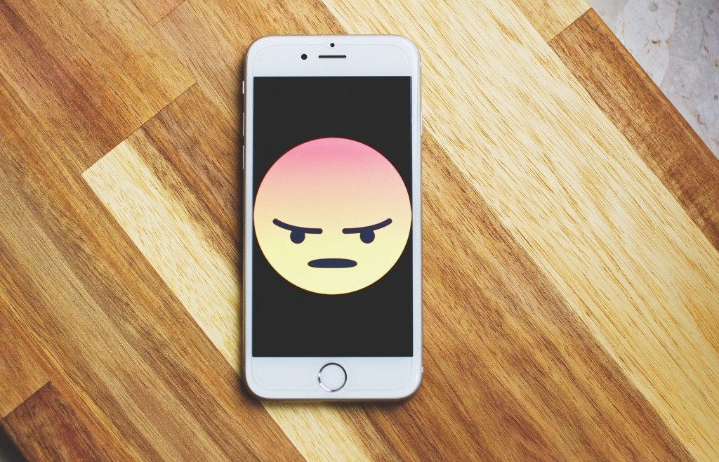Phone with an angry emoji on