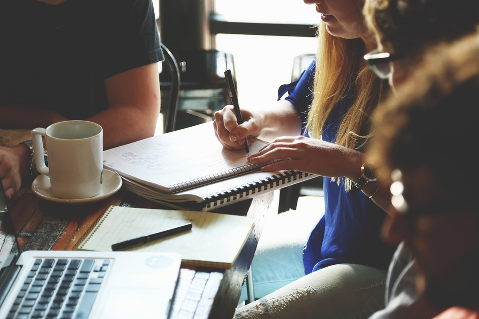 Image of young business types in a meeting around a tabel