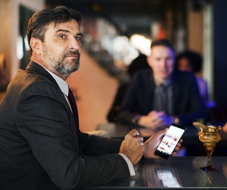 man on his phone at a bar looking very senior work figure