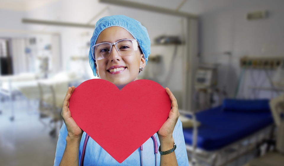 Nurse with a smile, holding a cut out paper love heart