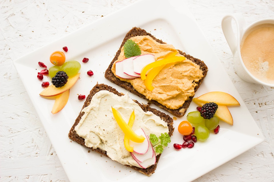Fruit on toast with a variety of different healthy looking spreads and extra fruit on the outside of the plate