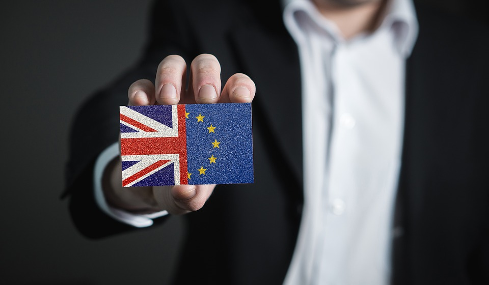 Businessman in a suit holding a business card held Union Jack half EU flag