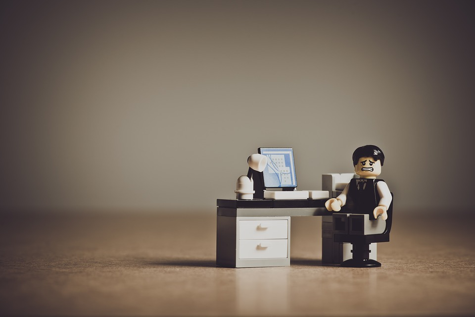 Lego man at a lego desk looking stressed