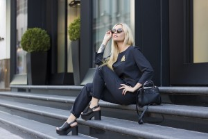 A stylish woman dressed in black and gold poses on some steps to represent high fashion and designer labels