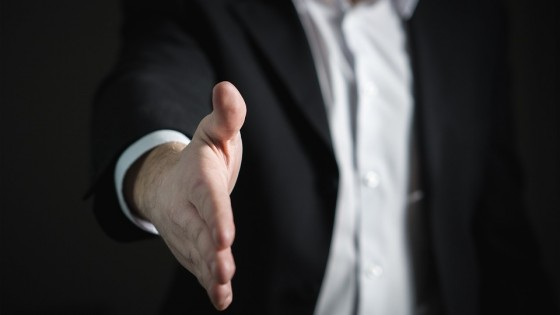 A man in a suit offering his hand out, in a handshake to say 'you got the job'