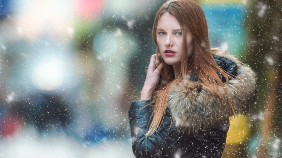 Woman in snow facing camera looking annoyed