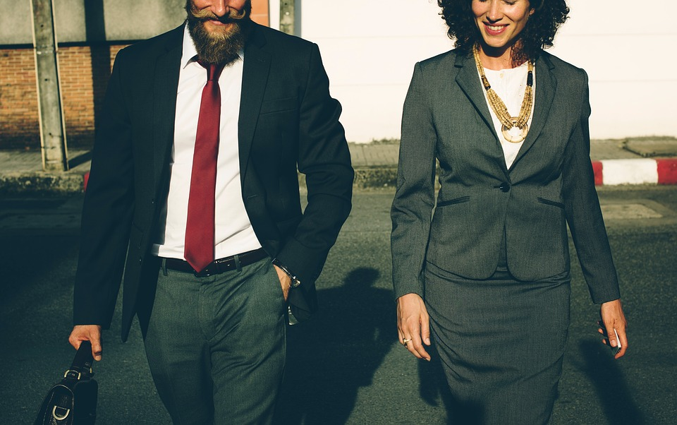 Man and woman in suit walking towards the camera in a business like fashion