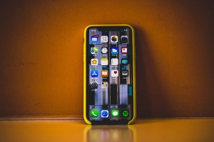 Iphone XR with apps - phone is yellow and orange sunburnt background