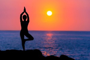 woman doing yoga on a rock by the ocean with a deep red sunset