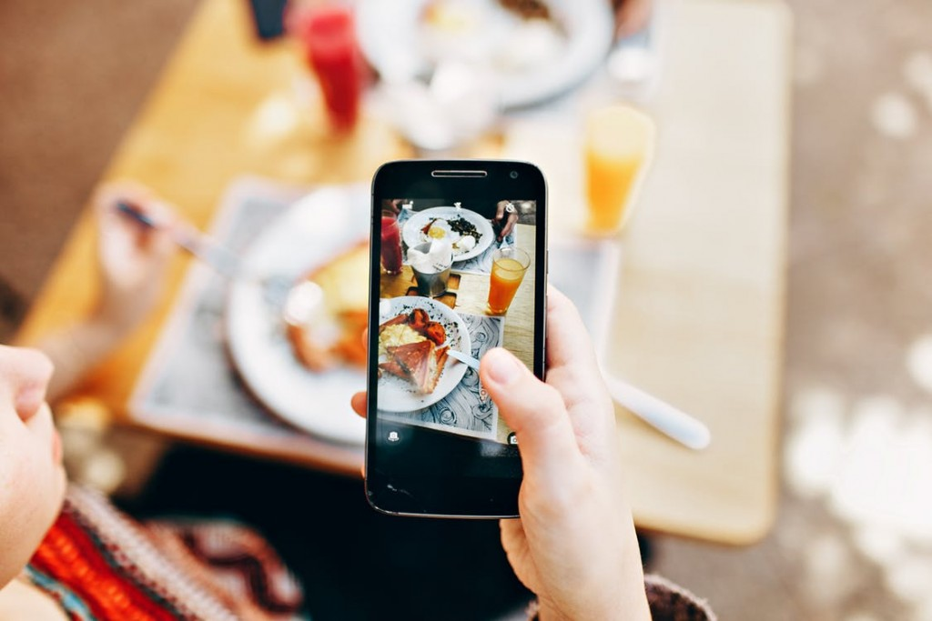 smartphone taking a photo of a breakfast meal with orange juice