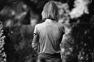 Woman standing along in black and white, back to camera
